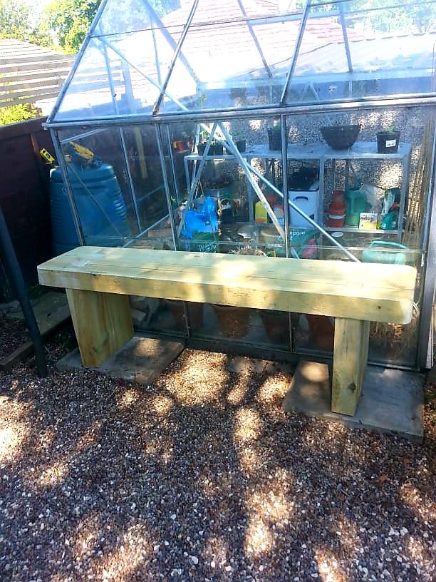Garden bench next to greenhouse
